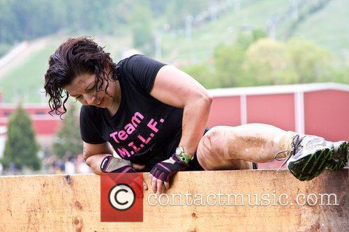 A Tough Mudder Participant Climbs The 'berlin Wall' Section Of The Course. 6