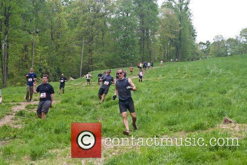 Tough Mudder Participants Run Down Hill Through The Course. 7