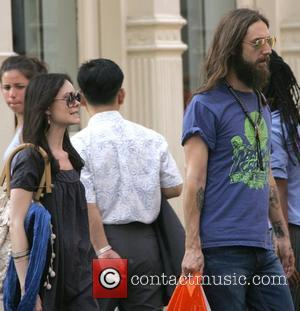 Chris Robinson of the Black Crowes walking in SoHo in sandals with his new girlfriend close behind him New York...