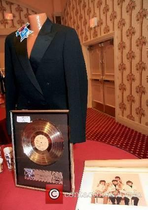 A John Lennon formal jacket and Capital Records gold record given to the Beatles for 1,000,000 records sold, and their...
