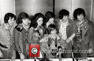 Shown (in center starting third from left): Marie Osmond, Jimmy Osmond (front), and Donny Osmond (rear) circa 1975