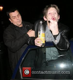 Shane McGowan of The Pogues, drinking Schweppes Tonic Water from a bottle, and shouting abuse at photographers as he leaves...