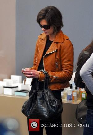 Katie Holmes checking her Blackberry while shopping at The Corner at Gendarmenmarkt. She bought the brown leather jacket she's wearing...