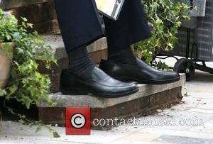 Nicolas Cage wearing oversized shoes when enjoying a break from filming on location in Primrose Hill for his latest movie...