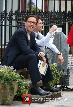 Nicolas Cage reading a book on set whilst on a break from filming on location in Primrose Hill for his...