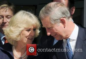Prince Charles, Prince of Wales, wearing a Jewish yarmulka, and Camilla, Duchess of Cornwall smile at each other when they...