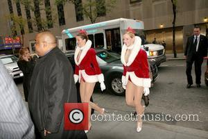 Two Radio City Rockettes  exit Radio City Music Hall and cross 50th Street to attend the USO awards at...