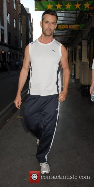 Rupert Everett sporting track suit bottoms and athletes top walking in Covent Garden London, England - 18.07.07