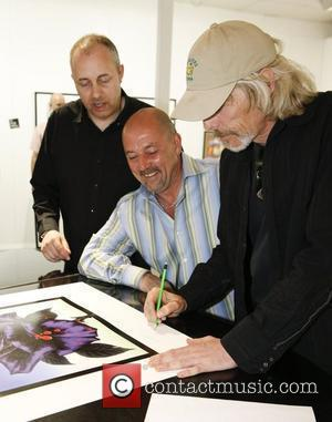 Scott Gorham of Thin Lizzy signs a limited edition print of the Black Rose album cover at St. Pauls Gallery...