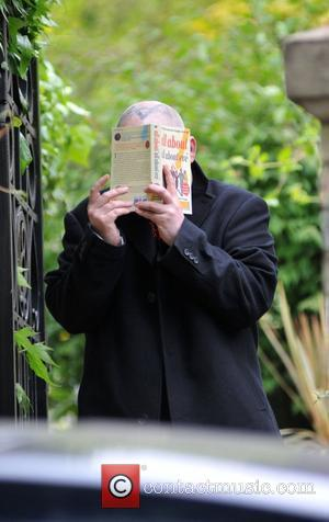 Boy George aka George O'Dowd leaves his home holding a copy of 'All About All About Eve' to cover his...