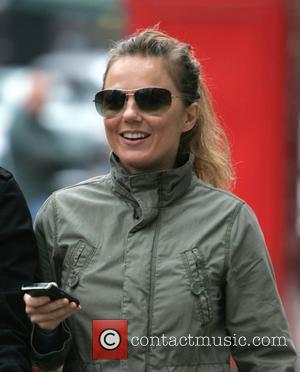 Geri Halliwell smiling and using a mobile device while out and about with her daughter in London.  Lodnon, England...