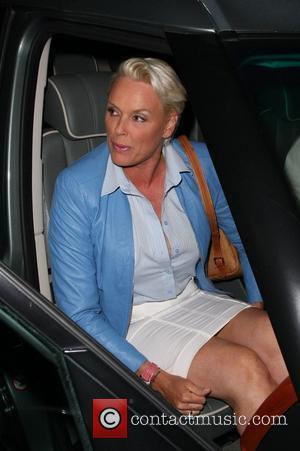 Brigitte Nielsen pulls down her skirt after revealing her Spanx (support underwear) while leaving Madeo restaurant where she had dinner...