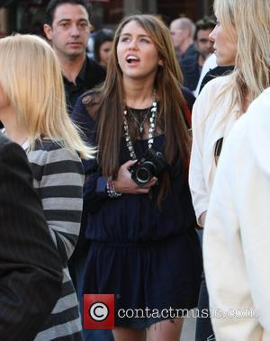 Miley Cyrus leaving The Grove after a book signing with her boyfriend Justin Gaston. Miley seen holding a camera takes...