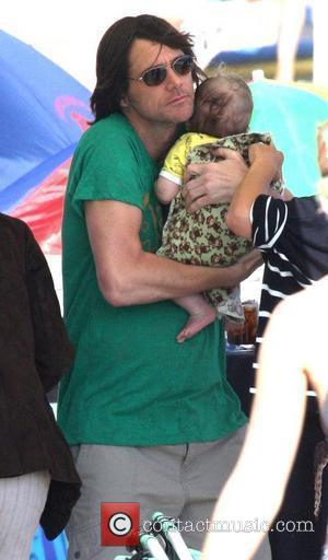 Jim Carrey holding his grandson Jackson Santan on Malibu Beach Malibu, California - 04.07.10