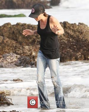 Victoria Beckham  gets her feet and jeans wet in the water on the beach Malibu, USA - 31.01.10