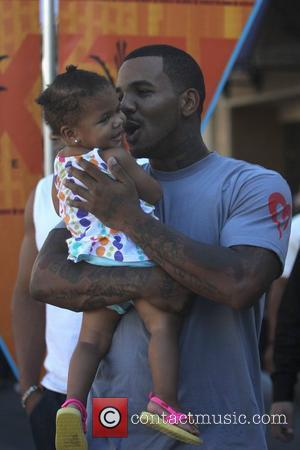 Rapper The Game aka Jayceon Terrell Taylor holds his daughter at The Grove to film an appearance for the entertainment...