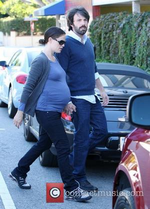 A heavily pregnant Jennifer Garner and husband Ben Affleck holding hands as they cross the road together  Brentwood, California...
