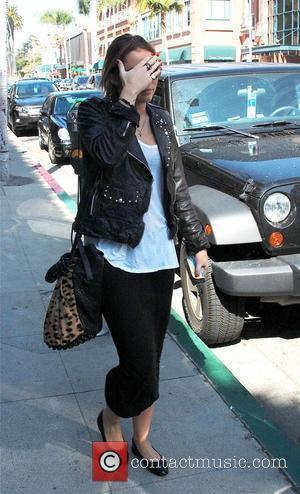 Miley Cyrus holds her hand to her face to escape having her picture taken as she walks along a sidewalk...