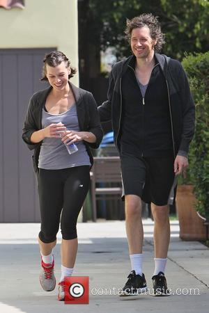Milla Jovovich and her husband seem in good spirits as they leave their personal trainer together in West Hollywood Los...