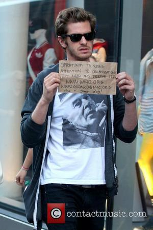 Andrew Garfield And Emma Stone Hold Up Charity Signs For Snappers
