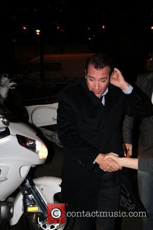 Heroes' Welcome As Jean Dujardin Carries Oscar Through Paris Airport