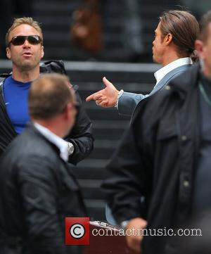 Brad Pitt  on location of his new movie 'The Counselor' gesturing a gun sign with his hand before he...