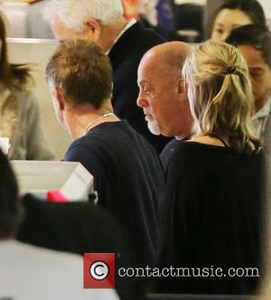 Billy Joel and Wife Alexis Roderick - Billy Joel and his wife Alexis Roderick passes through airport security at Los...