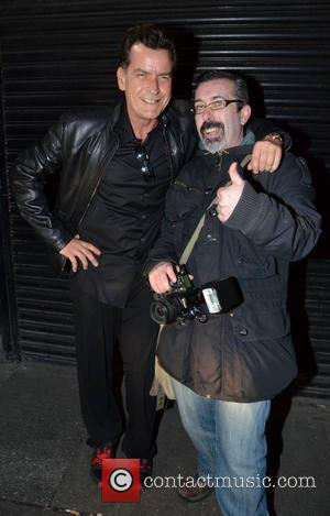 Charlie Sheen - Charlie Sheen poses for the cameras with a paparazzi photographer before attending the Slash concert at the...