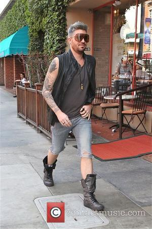 Adam Lambert - Singer Adam Lambert looks fashionable in knee length denim shorts, boots and sleeveless black leather waist jacket...