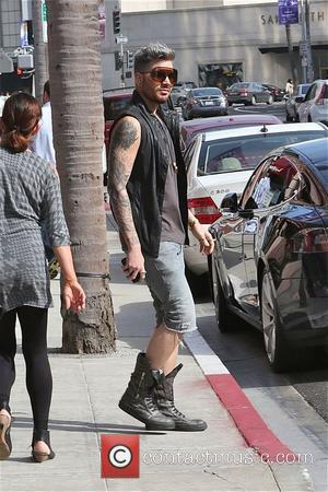 Adam Lambert - Singer Adam Lambert looks fashionable in knee length denim shorts, boots and sleeveless black leather waist jacket...