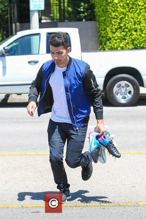 Joe Jonas - Joe Jonas carries his soccer boots before heading to watch the United States men's national soccer team...