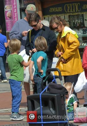 Cillian Murphy, wife Yvonne McGuinness and their sons Malachy and Aran Murphy watch break-dance buskers Dublin City BBoys on Grafton...