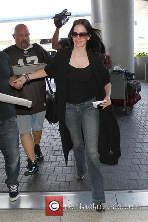 Eva Green - Eva Green at Los Angeles International Airport wearing a black top with grey jeans and a long...