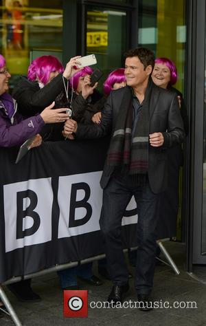 Donny Osmond - Donny Osmond leaves the BBC Breakfast studios at MediaCityUK. A small group of fans wear purple wigs...