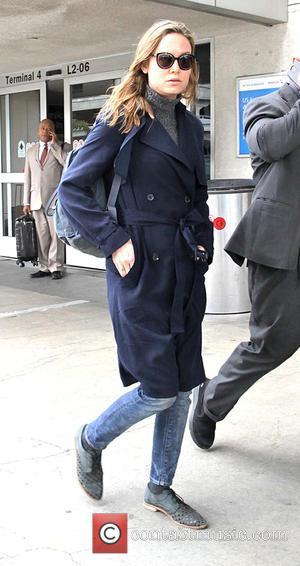 Brie Larson - Brie Larson arrives at Los Angeles International Airport (LAX) wearing all blue. Blue raincoat, blue jeans; blue...
