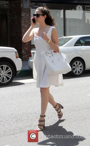 Emmy Rossum - Emmy Rossum dressed in a white siummer dress with white oversized handbag and strappy brown heels goes...