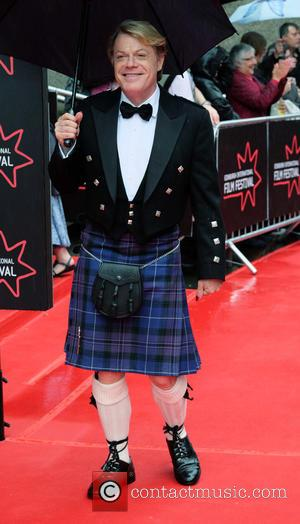 Eddie Izzard dressed in a kilt sheltering from the rain under an umbrella at the Edinburgh International Film Festival 2016...