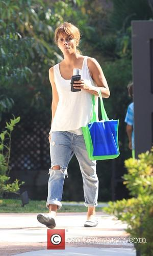 A make up free Halle Berry seen wearing a white vest top with ripped jeans while out and about in...