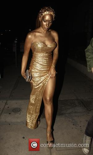 Leona Lewis steps out in head to toe gold as she attends a Halloween party with a male companion -...