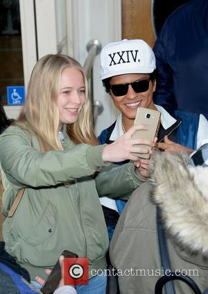 Bruno Mars signs memorabilia for fans outside Maida Vale after performing on the Radio One live lounge. - London, United...